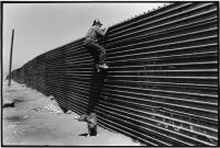 Tijuana--A worker looks over the fence between Mexico and the United States. © David Bacon