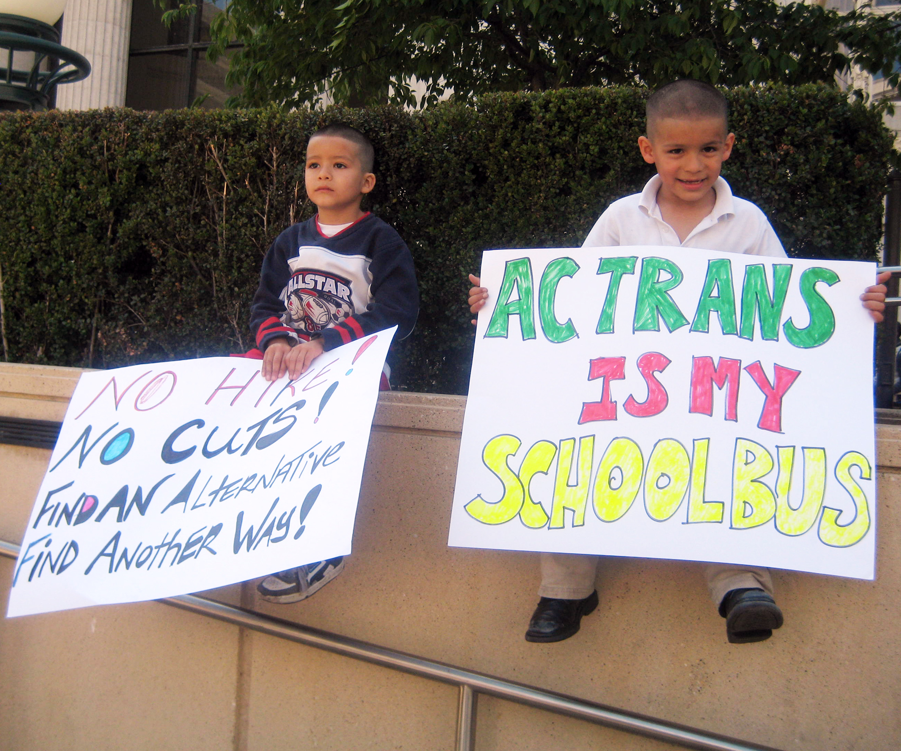 Jorge and Brian Solofzano hold signs at an AC Transit fare protest in October 2008. ©2008 Urban Habitat